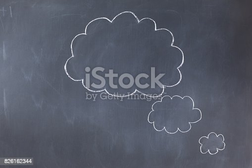 istock Empty cloud bubbles on a blackboard 826162344