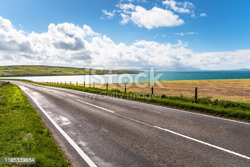 Deserted coast road along a beautiful bay on a clear summer day. Orkney Islands, Scotland, UK.