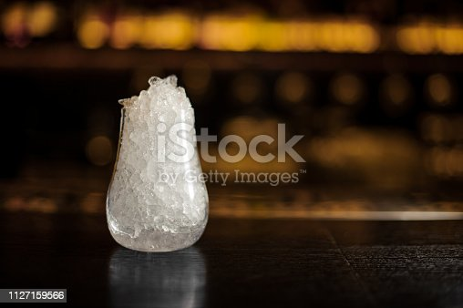 istock Empty cocktail glass filled with a lot of ice on the bar counter in blurred background 1127159566
