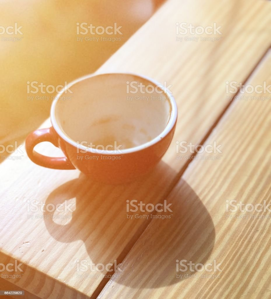 empty coffee cup on wood table with sunlight royalty-free stock photo