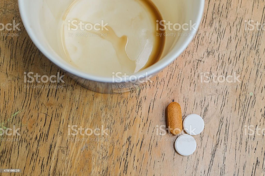empty coffee mug with medicine on wooden table stock photo