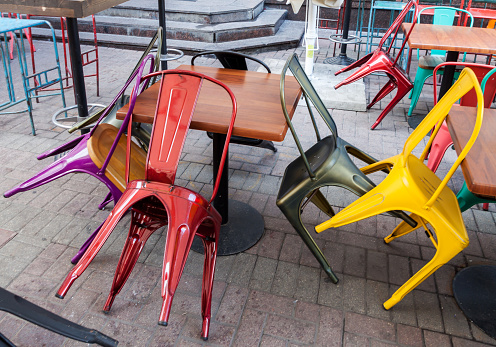 Empty color metal upturned chairs and tables at closed outdoor sidewalk pub