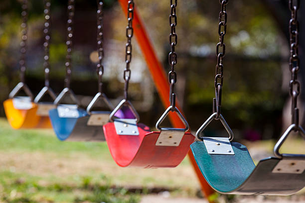 Empty colorful swings at the park stock photo