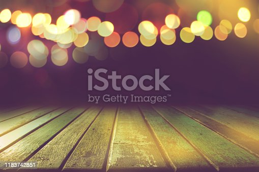 841276202istockphoto empty colour wooden table with bokeh light in dark night background 1183742851