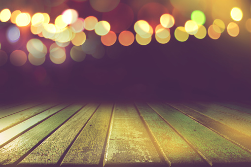 841276206 istock photo empty colour wooden table with bokeh light in dark night background 1183742851