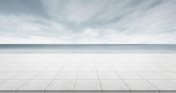 haut de la dalle de béton vide avec vue panoramique sur l'océan du ciel sombre du matin - show room photos et images de collection