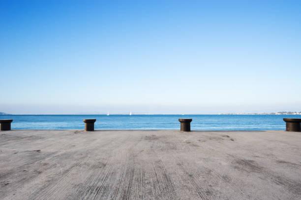 leere betonboden mit blauen meer im blauen himmel - zement terrasse stock-fotos und bilder