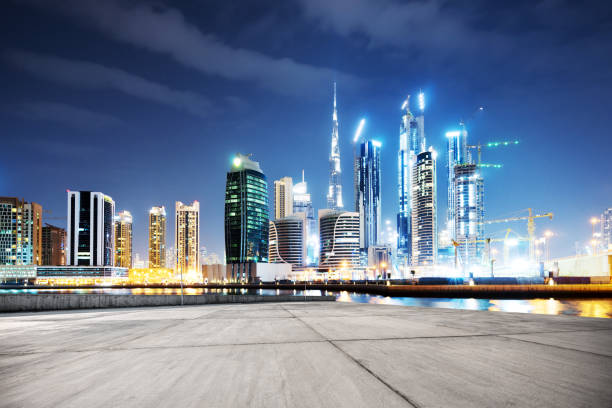 empty concrete floor with modern buildings at night stock photo