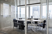 Empty chairs around table in board room. Modern meeting room against window in office. Furniture seen through glass walls in conference room.