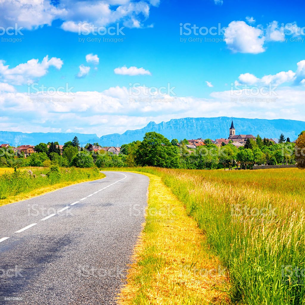 Empty counrtyside road with old french village and Alps mountains stock photo