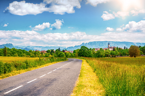 Empty countryside road with old french village and Alps mountains