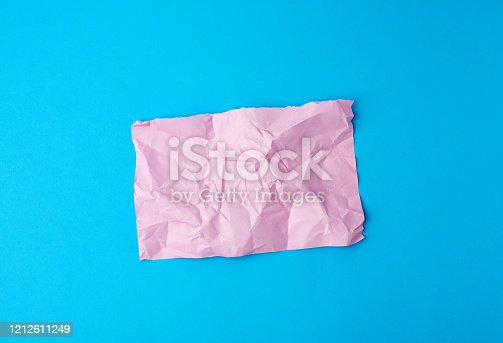 istock empty crumpled pink rectangular sheet of paper a4 on a blue background 1212611249