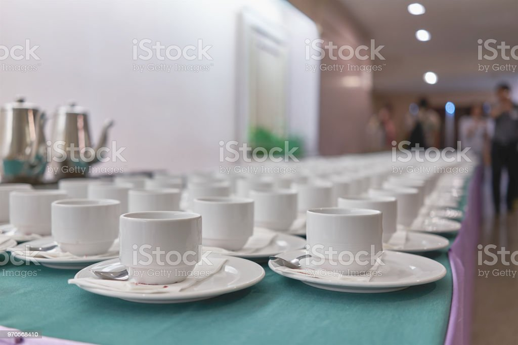 Empty white cups of coffee with spoon and tissue on saucer are placed...