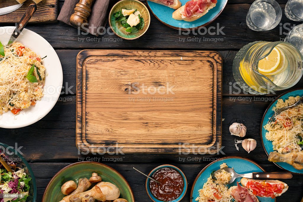 Empty cutting board on dark wooden table with variety food stock photo