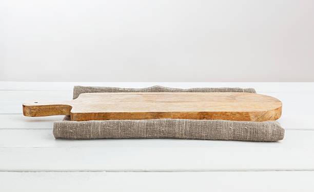 empty cutting board on white wooden table. - schnittkäse stock-fotos und bilder