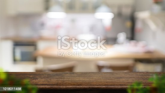istock Empty dark brown wooden table top with blurred home kitchen with blur foreground leaf,Mock up template for display or montage of your design,Banner for advertise of product,panorama view. 1018011458