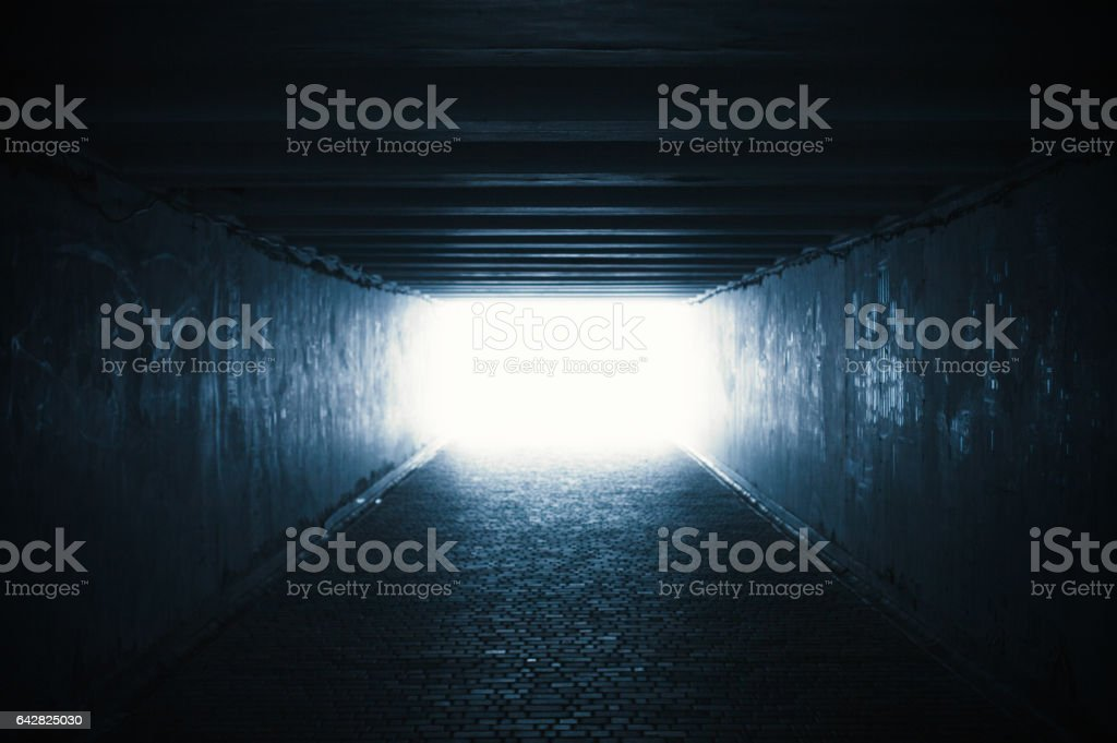 Empty dark tunnel with light in the end stock photo