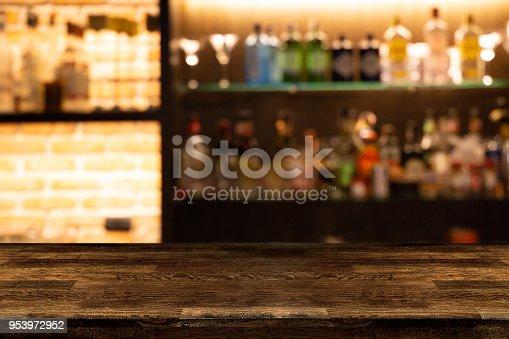 1013514594 istock photo Empty dark wooden bar counter with blur background bottles of restaurant. 953972952