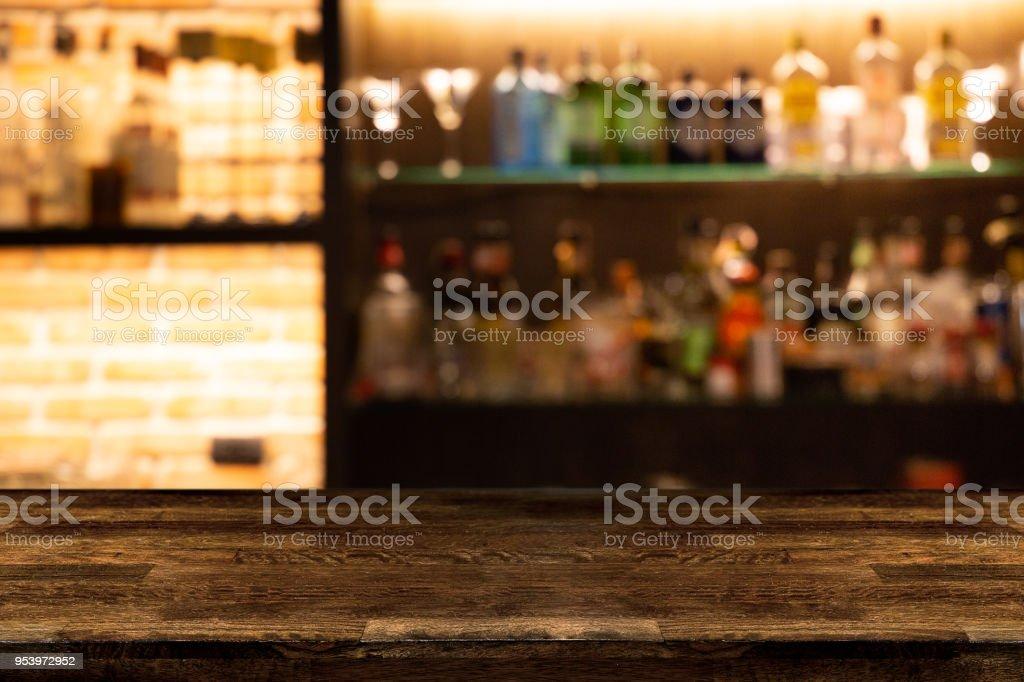 Lege donker houten toog met vervagen achtergrond flessen van restaurant. foto