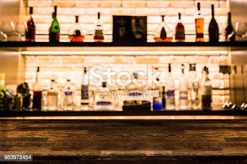 1013514594 istock photo Empty dark wooden bar counter with blur background bottles of restaurant. 953973454