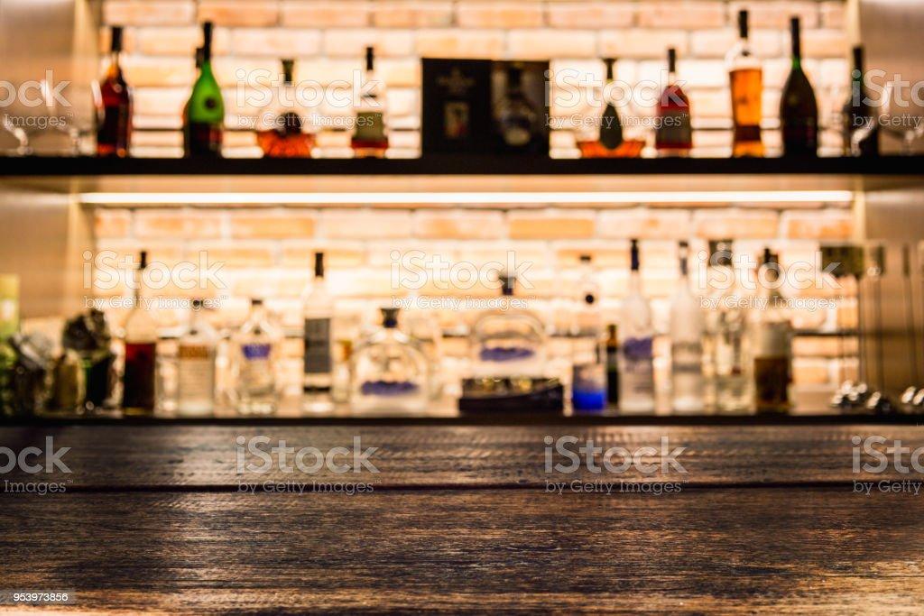 Empty dark wooden bar counter with blur background bottles of...