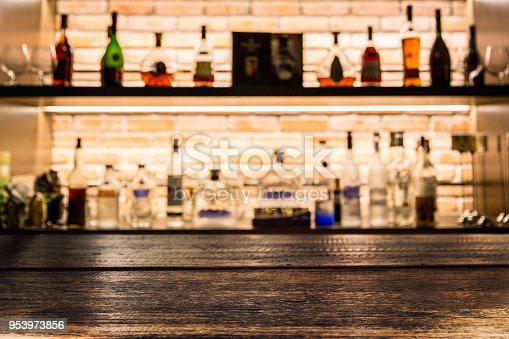 1013514594istockphoto Empty dark wooden bar counter with blur background bottles of restaurant. 953973856