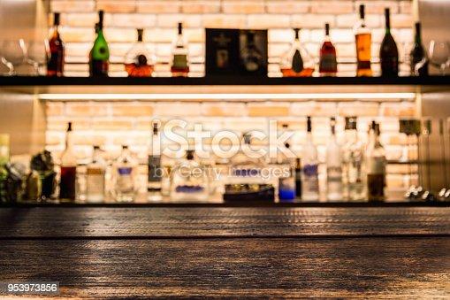 1013514594 istock photo Empty dark wooden bar counter with blur background bottles of restaurant. 953973856