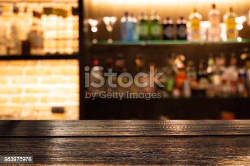 1013514594 istock photo Empty dark wooden bar counter with blur background bottles of restaurant. 953975976
