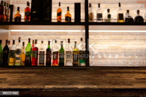 1013514594istockphoto Empty dark wooden bar counter with blur background bottles of restaurant. 990231692