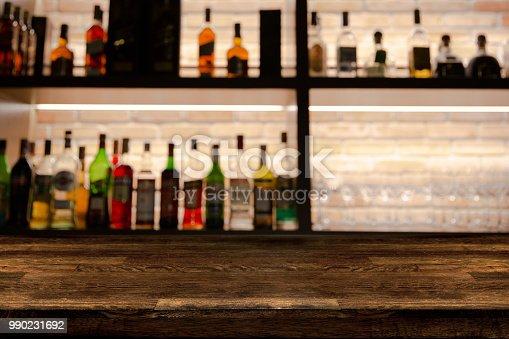 1013514594 istock photo Empty dark wooden bar counter with blur background bottles of restaurant. 990231692