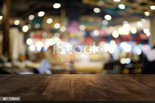 istock Empty dark wooden table in front of abstract blurred background of cafe and coffee shop interior. can be used for display or montage your products 961709942