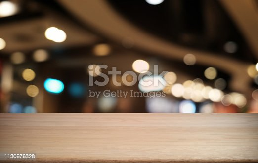 1077234988istockphoto Empty dark wooden table in front of abstract blurred bokeh background of restaurant . can be used for display or montage your products.Mock up for space. 1130676328