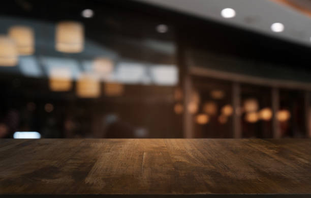 empty dark wooden table in front of abstract blurred bokeh background of restaurant . can be used for display or montage your products.mock up for space. - {{asset.href}} imagens e fotografias de stock