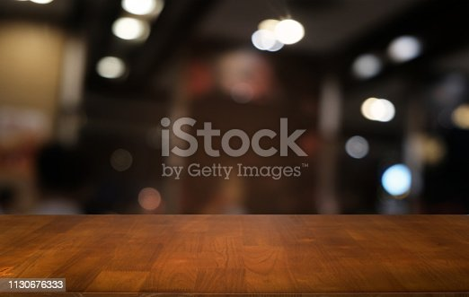 istock Empty dark wooden table in front of abstract blurred bokeh background of restaurant . can be used for display or montage your products.Mock up for space. 1130676333
