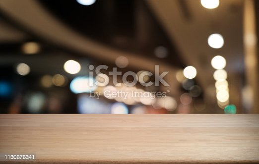 1077234988istockphoto Empty dark wooden table in front of abstract blurred bokeh background of restaurant . can be used for display or montage your products.Mock up for space. 1130676341
