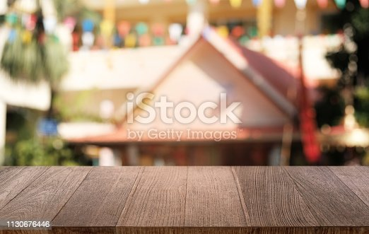 1077234988istockphoto Empty dark wooden table in front of abstract blurred bokeh background of restaurant . can be used for display or montage your products.Mock up for space. 1130676446