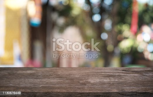 1077234988istockphoto Empty dark wooden table in front of abstract blurred bokeh background of restaurant . can be used for display or montage your products.Mock up for space. 1130676449