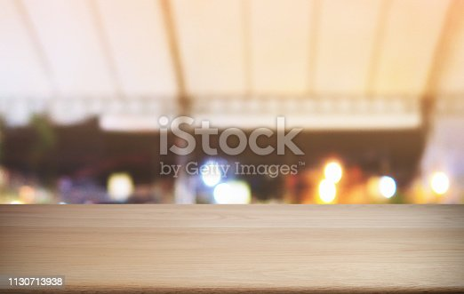 1077234988istockphoto Empty dark wooden table in front of abstract blurred bokeh background of restaurant . can be used for display or montage your products.Mock up for space. 1130713938