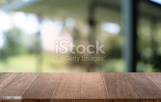 1077234988istockphoto Empty dark wooden table in front of abstract blurred bokeh background of restaurant . can be used for display or montage your products.Mock up for space. 1130713952