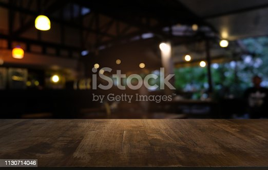 istock Empty dark wooden table in front of abstract blurred bokeh background of restaurant . can be used for display or montage your products.Mock up for space. 1130714046