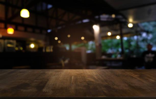 tavolo vuoto in legno scuro di fronte a uno sfondo bokeh sfocato astratto del ristorante. può essere utilizzato per visualizzare o montare i tuoi prodotti. prendi in giro per lo spazio. - mercato luogo per il commercio foto e immagini stock