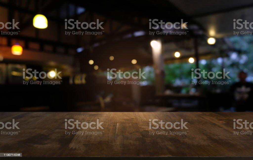 Mesa de madeira escura vazia na frente de fundo abstrato bokeh turva do restaurante. pode ser usado para exibir ou montagem de seus produtos. Zombe-se para o espaço. - foto de acervo