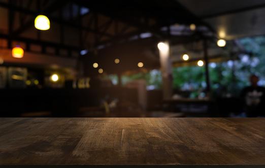Lege Donkere Houten Tafel Voor Abstracte Wazig Bokeh Achtergrond Van Restaurant Kan Worden Gebruikt Voor Weergave Of Montage Van Uw Producten Bespotten Voor Ruimte Stockfoto en meer beelden van Abstract