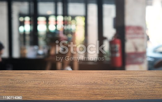 1077234988istockphoto Empty dark wooden table in front of abstract blurred bokeh background of restaurant . can be used for display or montage your products.Mock up for space. 1130714060