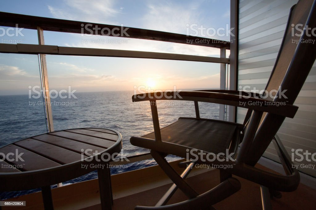 Empty Deck Chair on a Cruise Ship Balcony at Dusk stock photo