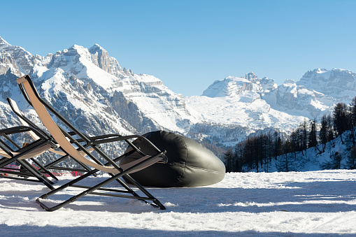 Empty deckchairs stand in the snow against the backdrop of snow-capped mountains. The concept of vacation, landscape.