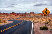 Empty desert road panorama surrounded by red rocks