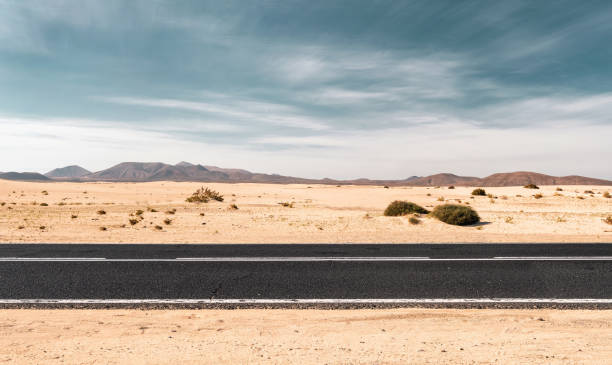Empty desert road with copy space Empty road through the desert dunes with copy space side view stock pictures, royalty-free photos & images