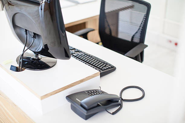 Empty desk with telephone, keyboard, computer and chair. Empty desk with telephone, keyboard, computer and chair. empty desk stock pictures, royalty-free photos & images