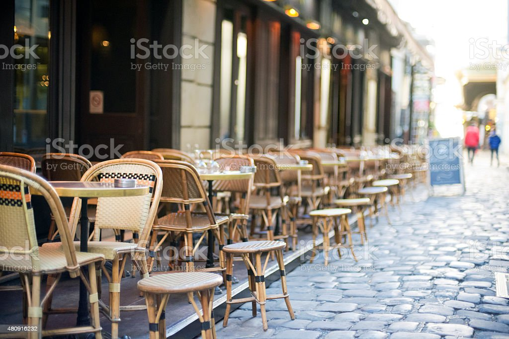Empty dining tables and chairs in Paris alley way stock photo